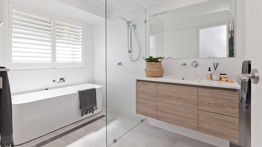 bathroom with wood cabinets and white bath