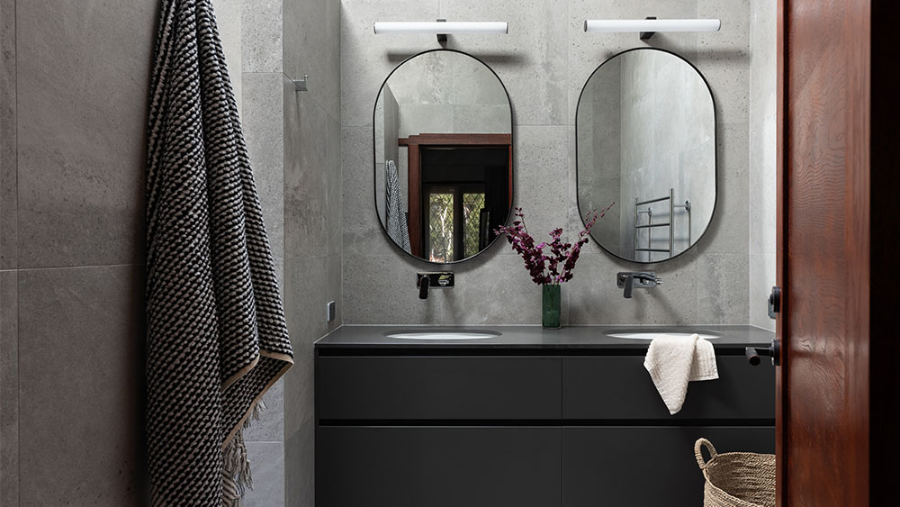 custom luxury bathrooms with dark tiling and a double vanity