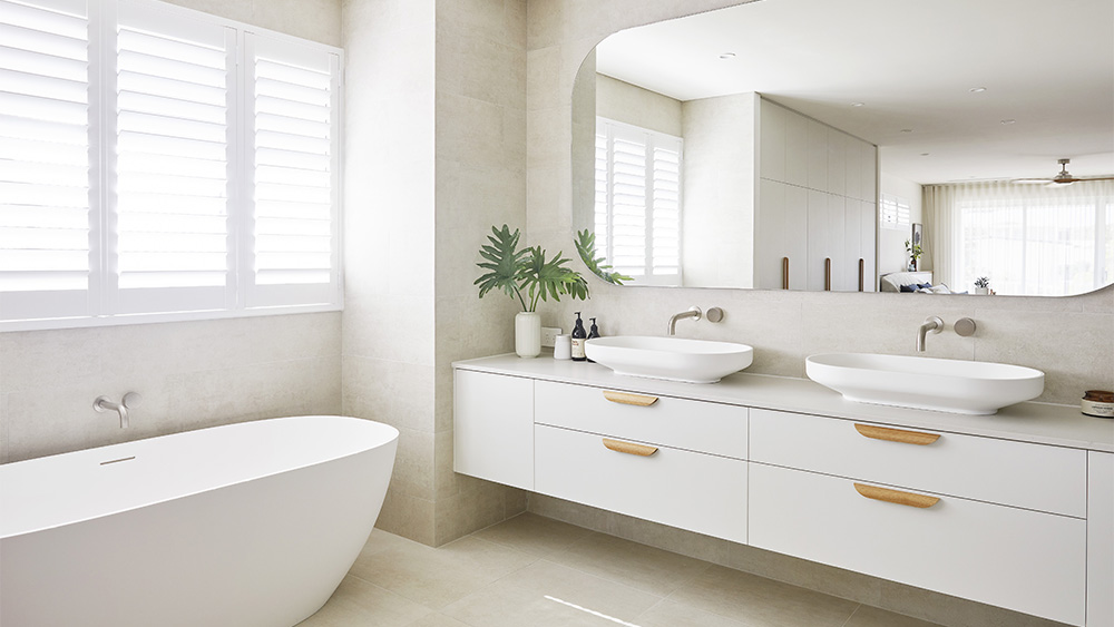 light and bright luxury bathroom with large mirror and shutter windows