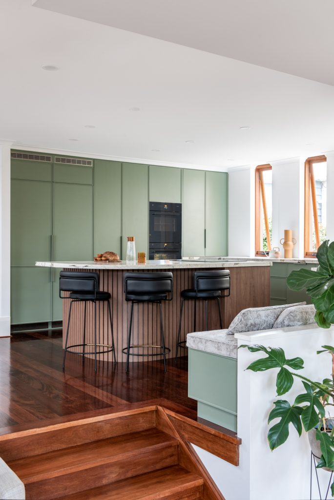 A long view of a renovated Perth kitchen showing wood floors, custom breakfast bar and green cabinets.