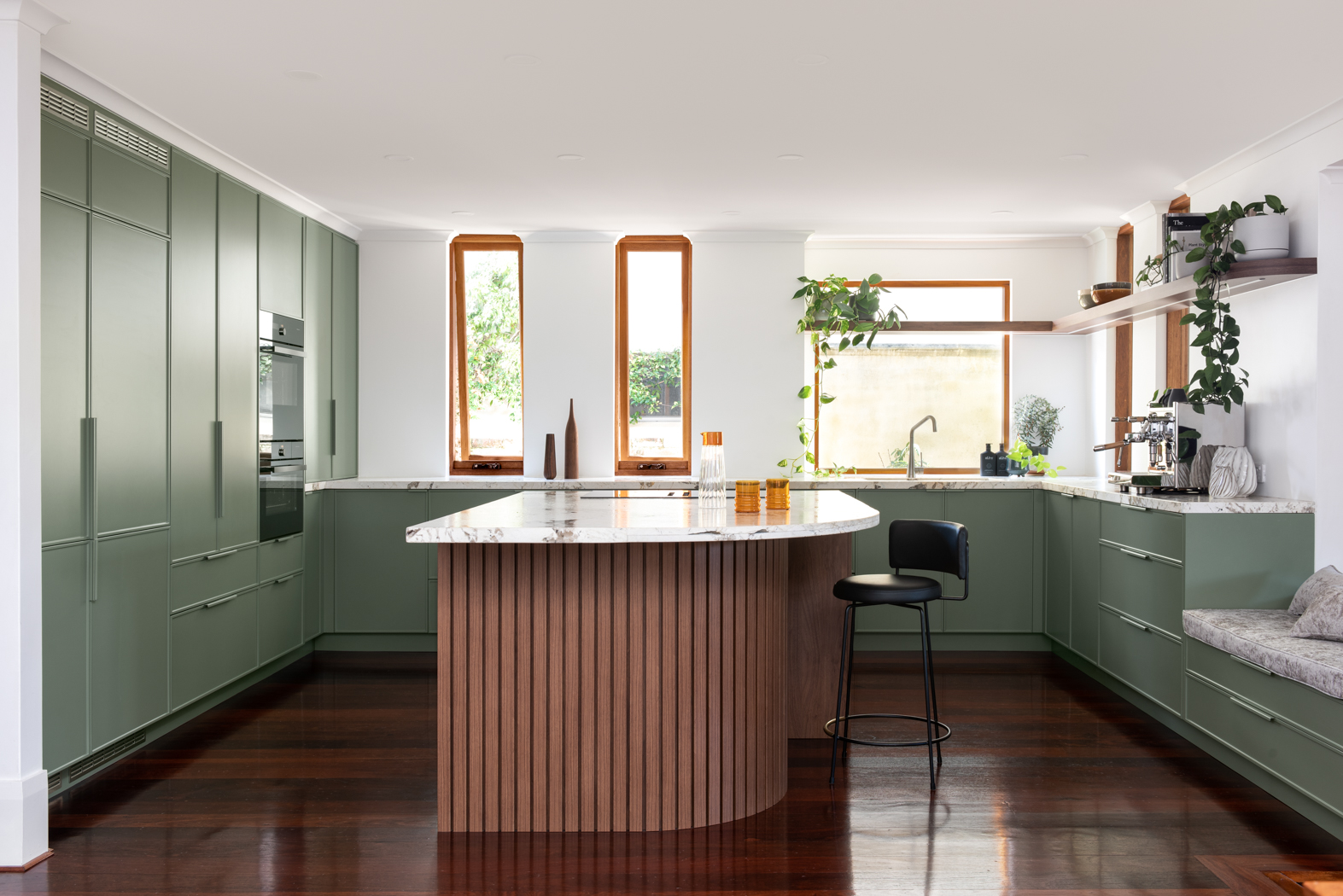 Renovated kitchen with wood floors, fern coloured cabinets and marble accents.